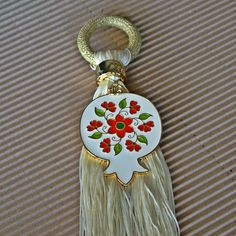 Ένα μπρούτζινο ρόδι με λευκό σμάλτο και ζωγραφισμένο ένα κόκκινο λουλούδι με πράσινα φύλλα. Έχει λευκή φούντα και χρυσό κορδόνι, για να το κρεμάτε ακόμα και στις πόρτες, για να φέρει καλοτυχία την νέα χρονιά.