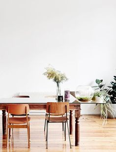 wood and glass table with house plants and mismatched chairs / sfgirlbybay