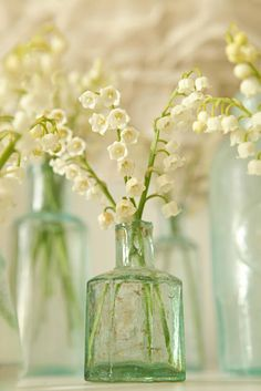 Sweet and simple — lily of the valley in green vintage bottles.