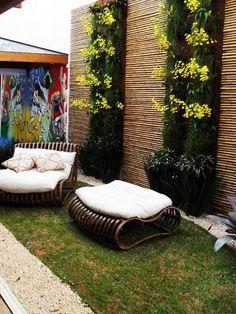 Jardim pequeno com paredes de bambu e flores verticais