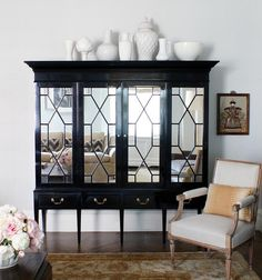 Elegant living room features a black armoire accented with mirrored doors atop sleek legs topped with a collection of white pottery alongside a bergere chair atop a gold Persian rug.