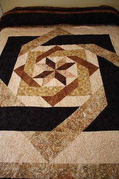 The name of this pattern is Labyrinth. I made it in shades of brown, gold, rust and tan. I wanted to have a quilt that looked a little more masculine but still look nice. It is 90 x 108. The back is very dark brown.