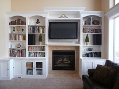 fireplace with hearth center bookcases on sides | entertainment bookcase wall unit with arched tops sample shown $ 2900