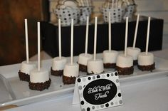 Marshmallows dipped in chocolate, covered in black sprinkles.