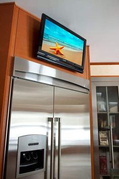 Kitchen With Stainless Steel And Mounted TV