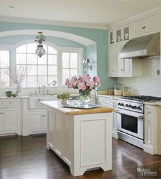 Create a serene kitchen setting with a light and cheery hue inspired by the sky. This airy, bright blue paint lightens the look of the deep espresso floors and complements the clean white cabinets, marble countertops, and classic subway tiles. Paint Color:Quietude SW612, Sherwin-Williams./