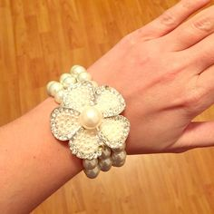 3 Strand Pearl flower bracelet Costume three stand pearl bracelet attached to flower pendant. Three rhinestones are missing from the flower but in otherwise great condition! Jewelry Bracelets