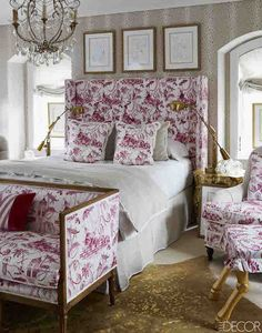 Megan Winters guest room in ELLE DECOR sneak peek. A pinky red plays a prominent role in the guest room as well, where a jubilant Lee Jofa toile and French vintage chandelier add a Parisian flair that Megan loves. The glamour of gold is a frequent feature in Megan's rooms and here a Kyle Bunting rug echoes the brass and gilded touches throughout.
