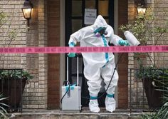 A member of the CG Environmental HazMat team disinfects the entrance to the residence of a health worker at the Texas Health Presbyterian Hospital who has contracted Ebola in Dallas, Texas, October 12, 2014. REUTERS/Jaime R. Carrero