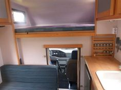 Interior of a Bimobil camper on a Fiat Ducato van, showing the cab-over bunk and kitchen cabinetry.