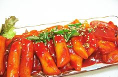 Ddukbokki (떡볶이): Spicy Korean rice cakes. Korean street food. I loved these and would watch them make them next to my sisters school while she was teaching.