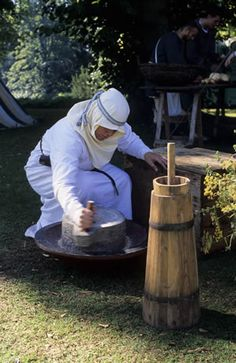 Grain being ground in a quern. In the foreground is a butter churn.