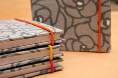 Cuadernos Entelados. Tamaño A5, 80 hojas, cosido y encuadernado a mano, tiene elastico de cierre al tono con las guardas. Colores: fuxia, naranja o amarillo.  Tambien formato libreta de 10x14 cm