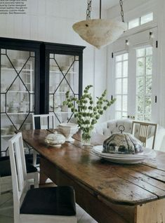 20 Great Shades of White Paint and Some To Avoid | fabulous sophisticated country dining area by Darryl Carter | love the china cabinet with the fretwork galss doors | Gustavian Swedish dining chairs and a rustic farm table | white walls.