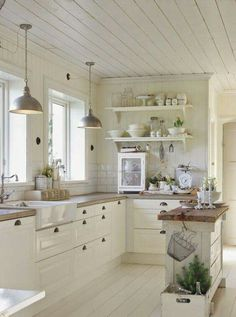 Wood countertops, white cupboards, white wood ceiling