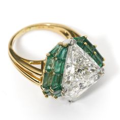 DIAMOND AND EMERALD RING, OSCAR HEYMAN & BROTHERS, 1993 Set with 2 triangular-shaped diamonds weighing 8.39 carats, framed by 24 baguette emeralds weighing 6.57 carats, mounted in 18 karat gold and platinum,