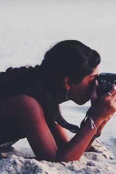 Woman in Black Tank Shirt Holding Camera during Daytime