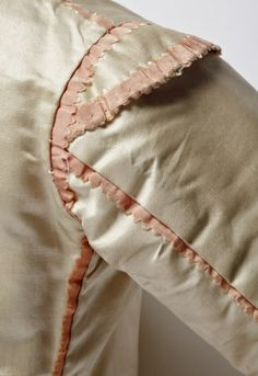 Jacket detail, back view of shoulder, child's 3-piece suit, probably Great Britain, 18th century. Ivory silk satin with pale pink silk trimming. (costume collection at Ham House, Surrey)