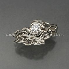 This is the two ring wedding set of our Delicate Leaf design. The engagement ring has two leaves wrapping a center Moissanite in a graceful manner. It