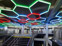 """This piece, which debuted in 2012 as part of a newly created in-station transfer, is one of the few light installations in the Arts for Transit program. According to Bloodworth, """"the majority of our projects are in durable materials,"""" such as ceramic and glass, since those are easier to maintain. But Villareal's honeycomb-shaped installation is a beauty: Neon LED lights flash in different colors, greeting passengers as they make the switch from one subway to another. (It's just begging to be…"""
