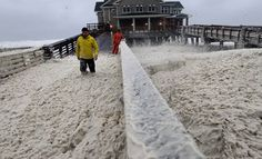 A news crew wades through sea foam blown onto Jeanette's Pier in Nags Head, North Carolina, on October 28, 2012 as wind and rain from Hurricane Sandy moved into the area. (AP Photo/Gerry Broome) #