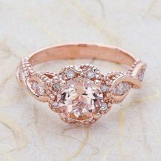 Ladies 14K Vintage rose gold engagement ring. The center is a 6.5 MM Round cut Morganite. side stones of .45ctw G color SI1 Clarity conflict free