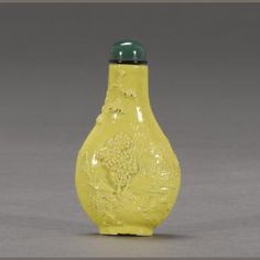 A yellow glazed porcelain carved 'landscape' snuff bottle