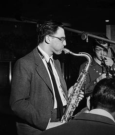 Profile image of American jazz musician Al Cohn playing the saxophone with two unidentified musicians.
