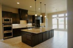 Large open kitchen, over sized island with breakfast bar, stainless steal appliances, granite counter tops, tumbled marble backsplash #mcbeehomes