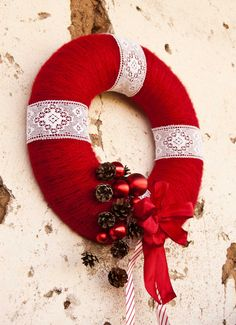 Christmas wreath made with red yarn, white lace, pine cones, ornaments, and ribbons || by Kaleda on Etsy
