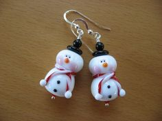 earrings are about 1 15/16 inches in length measuring from arch on top of earwires - snowman beads are handmade lampwork beads (about 20mm in length), 2 white snowballs with red and white scarves around the necks, faces have rosy cheeks, raised carrot noses and indented black eyes - red Swarovski crystals - black hat made with Czech glass rim and black onyx top - all other components are sterling silver