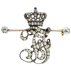 An Antique Diamond Brooch. An Antique Diamond Brooch, designed as intertwined initials 'FF', set with old European-cut diamonds, to the old European-cut diamond set crown surmount and cushion-cut diamond terminals, diamonds weighing 1.45 carats total, mounted in silver and gold, circa 1900. The initials 'FF' represent Austrian Archduke Franz Ferdinand.