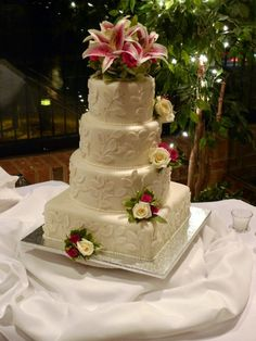 """All white fondant wedding cake decorated with pearl luster leaves and silver dragees.  The cake sizing is 6"""", 8"""", 10"""" and 12"""" tiers.  The cake is decorated with white and magenta roses and lillies.   The cake flavor is lemon cake with key lime cream cheese filling. Cakebee - Centreville, VA"""
