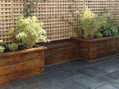 Hochbeete aus Holz und dunkelgraue Terrassenfliesen