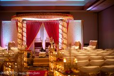 Red and gold circular mandap with crystal aisle via IndianWeddingSite.com