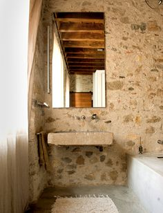 Two battered stone basins that may date to the 16th century were found on site, one buried under the house and another in a kitchen. They now serve as cantilevered bathroom sinks. (Barcelona home in NY Times)