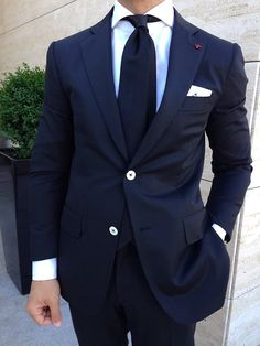 Navy blue suit paired with solid navy tie. What makes this look stand out are the white buttons and the coral lapel pin.