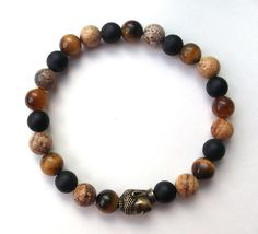 About the Bracelet An earthy men's beaded bracelet with a Buddha surrounded by multi-gemstones. Bracelet Details: This mens bracelet is made with: ★ 8mm Tiger Eye ★ 8mm Matte Black Onyx ★ 8mm Picture