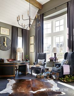 "A large antique clock, a chandelier from Circa Lighting, and walls painted Benjamin Moore's ""Rockport Gray"" make the room cozy and approachable. - Photo: Emily Jenkins Followill / Design: Amy Morris"
