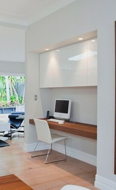 Minimalist home office nook with gloss white cabinetry and a walnut veneer desk & bulkhead with lighting