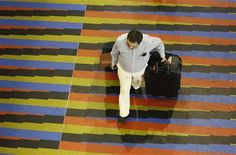 A passenger walks at the Simon Bolivar airport in La Guaira, outside Caracas September 23, 2013. REUTERS-Carlos Garcia Rawlins Flights out of Venezuela are overbooked but empty because of a traveler's allowance to buy dollars, which people can then resell on the black market.