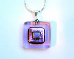 Paula Woodward  A  square fused glass pendant with lilac, magenta and purple layers. The base is a deep transparent lilac with layers of iridescent magenta and purple dichroic glass.