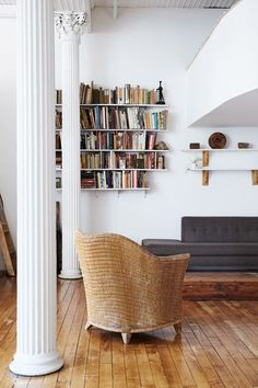 wicker chair and colorful books on display in white living room. / sfgirlbybay