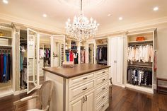 Antique white painted wood walk-in closet features an island dresser and plenty of double hanging storage. Note the special java glazing and classical embellishments such as decorative molding and acanthus leaf corbels.