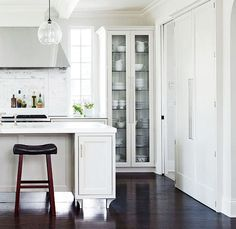 Streamlined classic kitchen.  Contemporary hardware, raised island, marble.