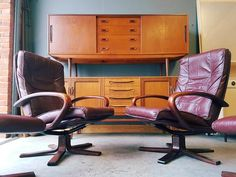 A fabulous pair of reclining burgundy red leather armchairs with matching footstools. Worn in all the right places, all four items are in very good condition for their age (mid century). The rosewood arms and pedestal legs complement the colour of the leather beautifully. Made by Kragelund, reputable Danish manufacturers, the label can still be seen under the seats. A wonderfully stylish, indicative of the period, collection of furniture.  M...