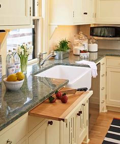 For easy cleanup, consider a slide-out chopping board that hovers near the sink and over a cabinet pullout with bins for trash and recycling. | Photo: Chad Holder | thisoldhouse.com