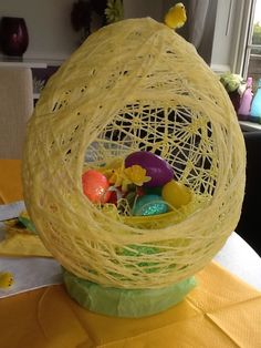 Large egg shaped decoration made with a balloon and yellow wool