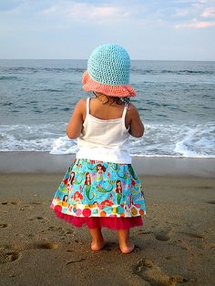 A little girl in a mermaid skirt looks out at the ocean. Photo for Palm Tree Princess on Etsy
