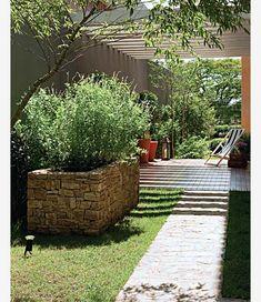 """Na lateral desta casa, uma vistosa horta foi montada numa caixa de pedra-madeira amarela (Margrape Comércio de Pedras) junto à área do deque, mas fora da sombra do pergolado. """"Escolhemos um espaço ensolarado e próximo do acesso à cozinha. Temperos pedem ao menos três horas de sol todo dia"""", detalha a paisagista Claudia Muñoz, da Línea Paisagismo."""